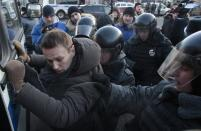 FILE - In this Saturday, Dec. 15, 2012 file photo, police officers detain opposition leader Alexei Navalny during an unauthorized rally in Lubyanka Square in Moscow. Navalny's energy and charisma propelled him from a lonely role blogging about corruption to widely renown as Russia's leading opposition activist. His projects, including a campaign to run for Moscow mayor, have attracted hordes of volunteers and fundraisers. Now comes a day that looms large for Navalny and the opposition: A court hands down its verdict Thursday in an embezzlement case that could send him to prison for six years. (AP Photo/Pavel Golovkin, File)