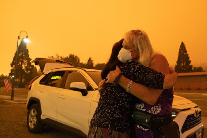 Evacuated residents hug near State Route 89 during the Dixie Fire in Greenville, Calif., on July 24. (David Odisho / Bloomberg via Getty Images)