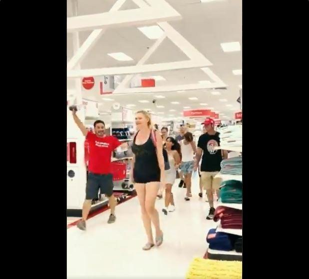 A group of anti-mask protesters march through a Target store in Florida blaring