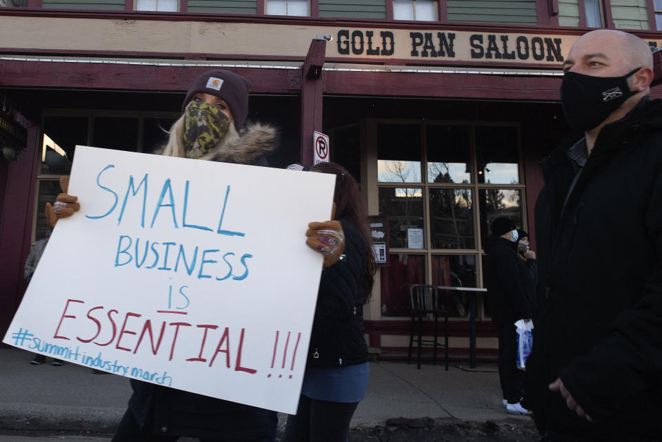Summit County service industry workers march past the Gold Pan Saloon while protesting the prohibition of in-person dining at restaurants Monday, Nov. 23, 2020 in Breckenridge, Colo. (Jason Connolly/Summit Daily News via AP)