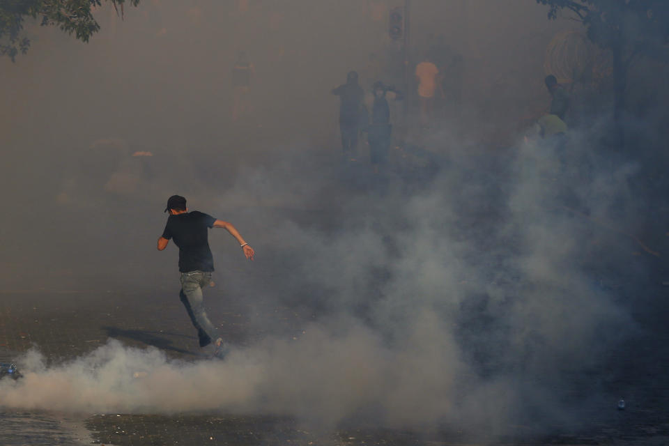 An anti-government protester runs amid tear gas fired by riot police during a protest marking the first anniversary of the massive blast at Beirut's port, near Parliament Square, In Beirut, Lebanon, Wednesday, Aug. 4, 2021. United in grief and anger, families of the victims and other Lebanese came out into the streets of Beirut on Wednesday to demand accountability as banks, businesses and government offices shuttered to mark one year since the horrific explosion. (AP Photo/Bilal Hussein)