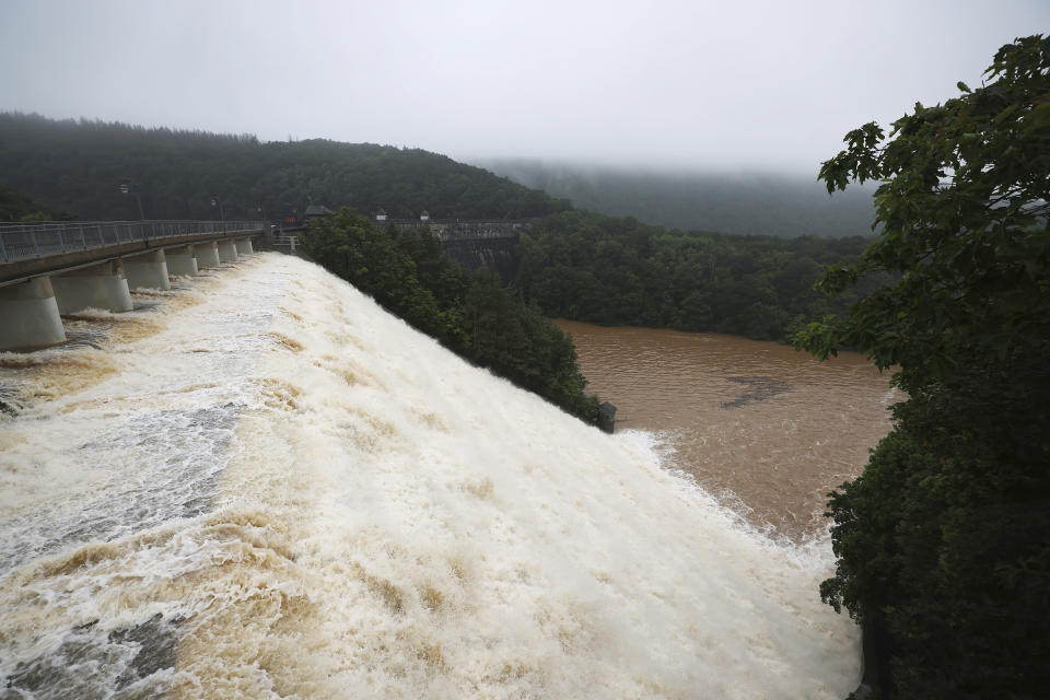 Water overflows the dam wall at the Urft reservoir in Gemuend, Germany, Friday, July 16, 2021 The flood situation in parts of the German state of North Rhine-Westphalia remains very tense. (Oliver Berg/dpa via AP)
