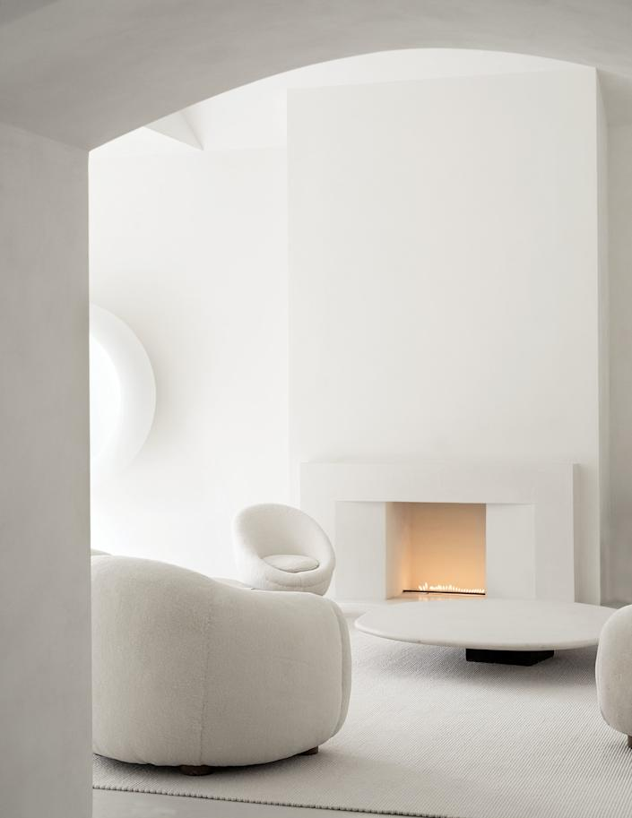 "<div class=""caption""> In the living room, Royère upholstered seating surrounds a limestone cocktail table by Axel Vervoordt. </div>"