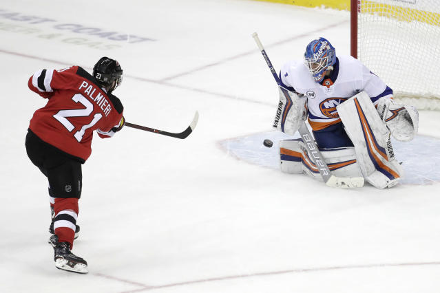 New Jersey Devils right wing Kyle Palmieri (21) misses a shot against New York Islanders goaltender Thomas Greiss, of Germany, during the shootout in an NHL hockey game Thursday, Feb. 7, 2019, in Newark, N.J. The Islanders won 2-1. (AP Photo/Julio Cortez)