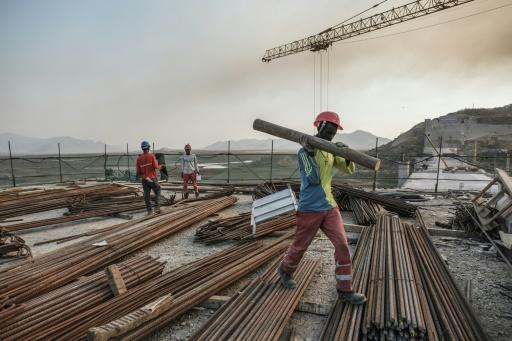 A worker walks with a piece of wood on his shoulder at the Grand Renaissance Dam, near Guba in Ethiopia