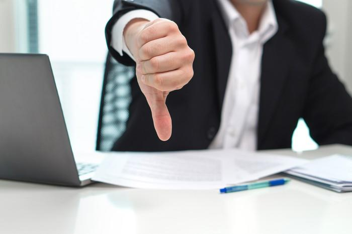 Businessman sitting in front of a laptop and making the thumbs down gesture with his right hand.