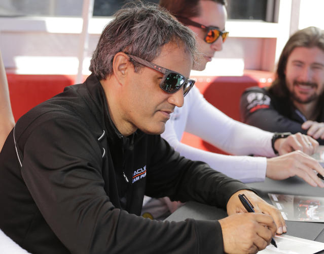 Acura Team Penske driver Juan Pablo Montoya signs autographs before the Rolex 24 hour auto race at Daytona International Speedway, Saturday, Jan. 25, 2020, in Daytona Beach, Fla. (AP Photo/Terry Renna)