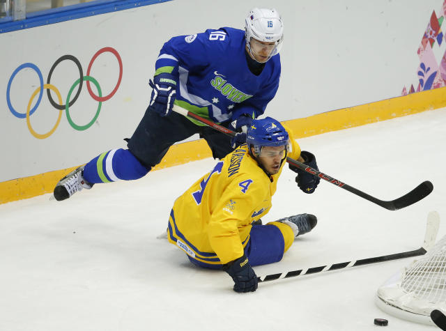 Sweden defenseman Niklas Hjalmarsson and Slovenia forward Ales Music battle for the puck in the first period of a men's quarterfinal ice hockey game at the 2014 Winter Olympics, Wednesday, Feb. 19, 2014, in Sochi, Russia. (AP Photo/Mark Humphrey)