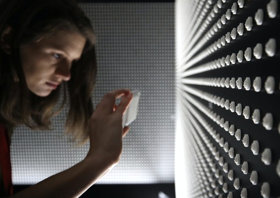 Cassie Spodak takes a picture of a memorial that consists of 22,000 engraved white pills that represent the face of someone lost to a prescription opioid overdose in 2015, at the Ellipse at President's Park, on April 11, 2018 in Washington, DC. (Photo: Getty)