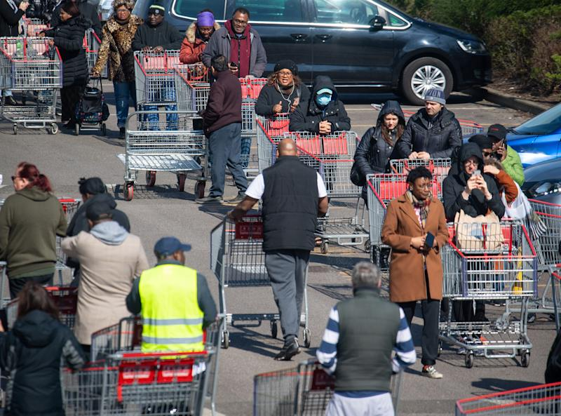 Shoppers queue outside a branch of Costco, in Croydon, south London, on the weekend after Prime Minister Boris Johnson ordered pubs and restaurants across the country to close as the Government announced unprecedented measures to cover the wages of workers who would otherwise lose their jobs due to the coronavirus outbreak. (Photo by Dominic Lipinski/PA Images via Getty Images)