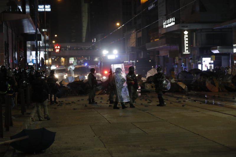 Police arrive to remove barricades set up by protestors in Hong Kong, Wednesday, Jan. 1, 2020. Hong Kong toned down its New Year's celebrations amid the protests that began in June and which have dealt severe blows to the city's retail, tourism and nightlife sectors. (AP Photo/Lee Jin-man)