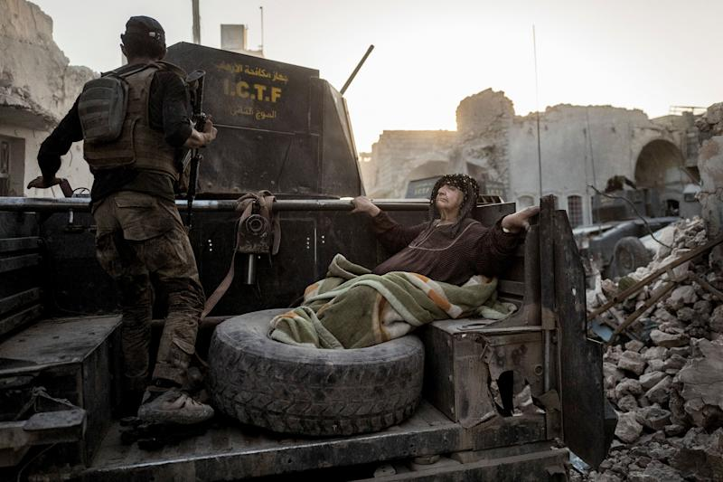 An elderly woman is driven through the city on the back of one of Golden Division's Humvees. The temperature is nearly 50 degrees Celcius, and she's too weak to get away from the frontline on her own.