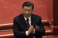 Chinese President Xi Jinping applauds during the closing session of the National People's Congress (NPC) at the Great Hall of the People in Beijing, Thursday, March 11, 2021. China's ceremonial legislature on Thursday endorsed the ruling Communist Party's latest move to tighten control over Hong Kong by reducing the role of its public in picking the territory's leaders. (AP Photo/Sam McNeil)