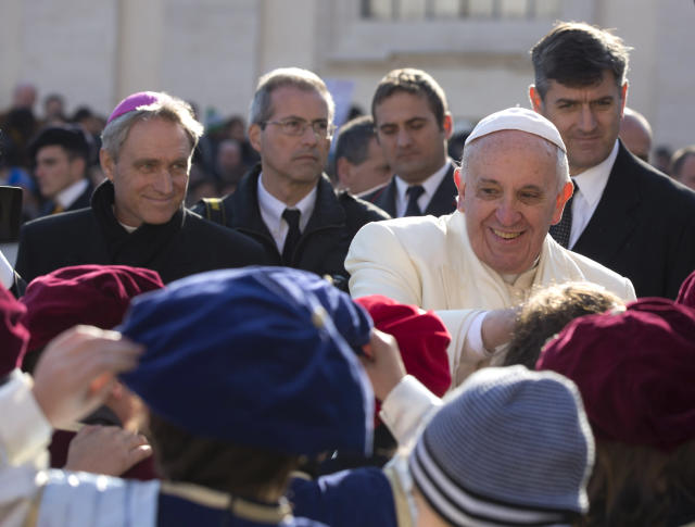 Pope Francis salutes children as he leaves after his weekly general audience in St. Peter's Square at the Vatican, Wednesday, Dec. 18, 2013. (AP Photo/Alessandra Tarantino)