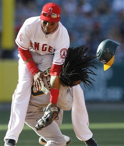 Oakland Athletics' Jemile Weeks steals second as Los Angeles Angels shortstop Erick Aybar fails to make the tag during the sixth inning of a baseball game in Anaheim, Calif., Tuesday, May 15, 2012. (AP Photo/Chris Carlson)
