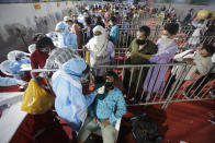 A health worker takes a nasal swab sample of a passenger to test for COVID-19 at a facility erected at a railway station to screen people coming from outside the city, in Ahmedabad, India, Friday, Sept. 18, 2020. India's coronavirus cases jumped by another 96,424 in the past 24 hours, showing little sign of leveling. India is expected to have the highest number of confirmed cases within weeks, surpassing the United States, where more than 6.67 million people have been infected. (AP Photo/Ajit Solanki)