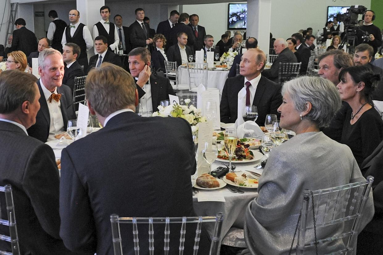 Russian President Vladimir Putin, center right, with retired U.S. Lt. Gen. Michael T. Flynn, center left, and Serbian filmmaker Emir Kusturica, obscured, second right, attend an exhibition marking the 10th anniversary of RT (Russia Today), the 24-hour English-language TV news channel in Moscow, on Dec. 10, 2015. (Photo: Mikhail Klimentyev/Sputnik, Kremlin Pool Photo via AP)