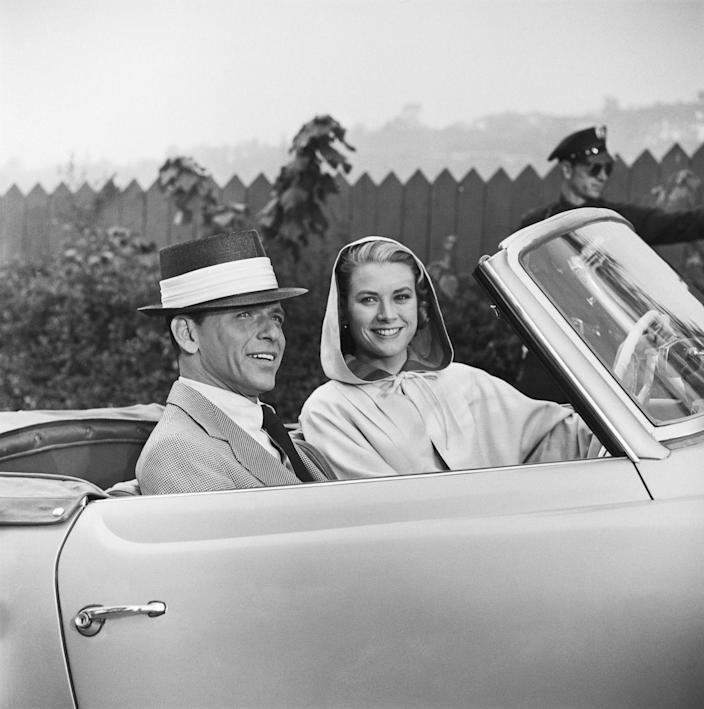 """<p>Kelly and Frank Sinatra ride in a convertible while filming a scene for<em> High Society</em>. The actress shared a duet with the famous crooner in the film, which <a href=""""https://www.imdb.com/title/tt0049314/trivia"""" rel=""""nofollow noopener"""" target=""""_blank"""" data-ylk=""""slk:earned her a gold record"""" class=""""link rapid-noclick-resp"""">earned her a gold record</a>. </p>"""