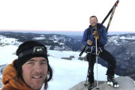 """In this photo provided by Jason Torlano, he poses with his friend, Zach Milligan, right, on Half Dome in Yosemite National Park, Calif., on Sunday, Feb. 21, 2021. Two men climbed some 4,000 feet to the top of Yosemite's Half Dome in subfreezing temperatures and skied down the famously steep monolith to the valley floor. Torlano, 45, and Milligan, 40, completed the daring descent in five hours on Sunday by charging down Half Dome's arching back and using ropes to rappel down several sections of bare rock known as the """"death slabs,"""" the Fresno Bee reported on Thursday. (Jason Torlano via AP)"""