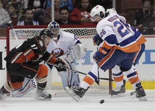 New York Islanders left wing Matt Moulson, right, and Anaheim Ducks center Saku Koivu, left, of Finland, look at a puck during the first period of an NHL hockey game in Anaheim, Calif., Friday, Jan. 6, 2012. (AP Photo/Jae C. Hong)