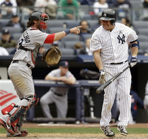 Boston Red Sox catcher Jarrod Saltalamacchia gestures to the pitcher as New York Yankees' Kevin Youkilis reacts after a seventh-inning strikeout stranding two runners in an opening day baseball game at Yankee Stadium in New York, Monday, April 1, 2013. (AP Photo/Kathy Willens)