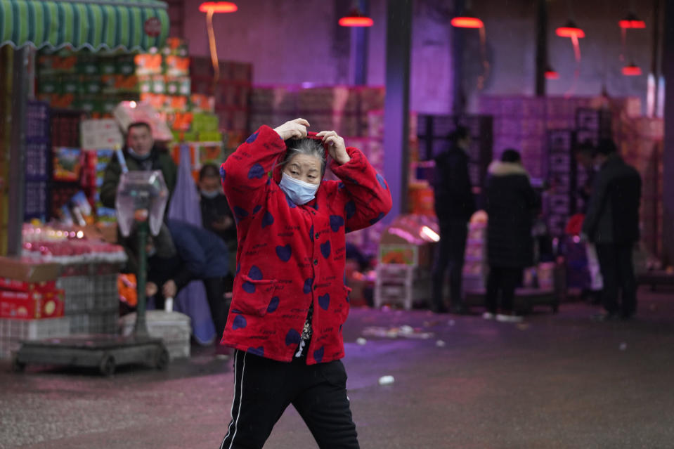 A woman wearing her mask walks past a fruit market near the Huanan Seafood Market in Wuhan, China, Sunday, Jan. 31, 2021. Scientists initially suspected the coronavirus came from wild animals sold in the market. The market has since been largely ruled out but for the visiting WHO team of international researchers it could still provide hints to how the virus spread so widely. (AP Photo/Ng Han Guan)