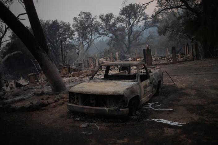 The remains of a vehicle and home are seen in the aftermath of the Glass Fire in Deer Park, California