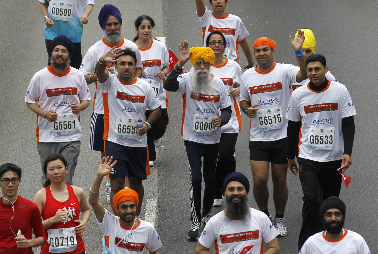 Centenarian marathon runner Fauja Singh, 101, center, originally from Beas Pind, in Jalandhar, India but who now lives in London, runs in a 10-kilometer race, part of the annual Hong Kong Marathon, in Hong Kong Sunday, Feb. 24, 2013. Singh will retire from public racing after competing in the marathon. (AP Photo/Kin Cheung)