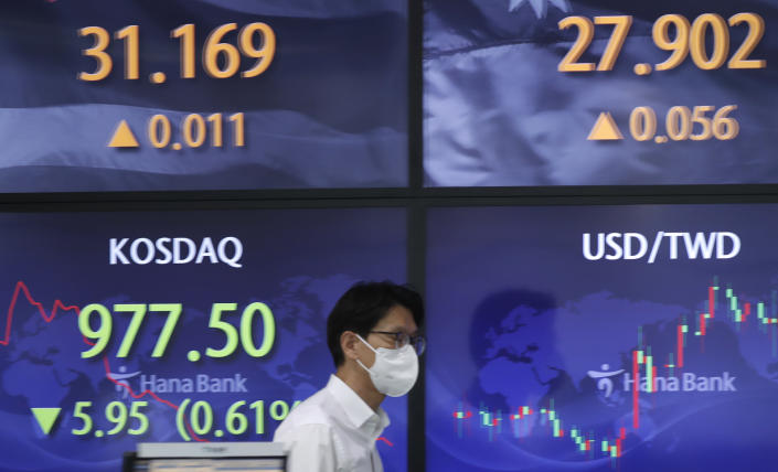 A currency trader walks near screens showing the Korean Securities Dealers Automated Quotations (KOSDAQ), left bottom, and the foreign exchange rates at a bank's foreign exchange dealing room in Seoul, South Korea, Monday, May 3, 2021. Shares were mostly lower in Asia in thin trading Monday, with many markets including those in Tokyo and Shanghai closed for holidays. (AP Photo/Lee Jin-man)