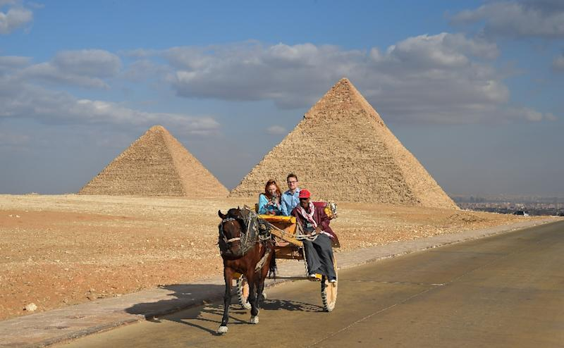 An Egyptian drives a horse-drawn cart with a couple of tourists at the Giza pyramids on the southwestern outskirts of the Egyptian capital Cairo on December 29, 2018 (AFP Photo/MOHAMED EL-SHAHED                   )