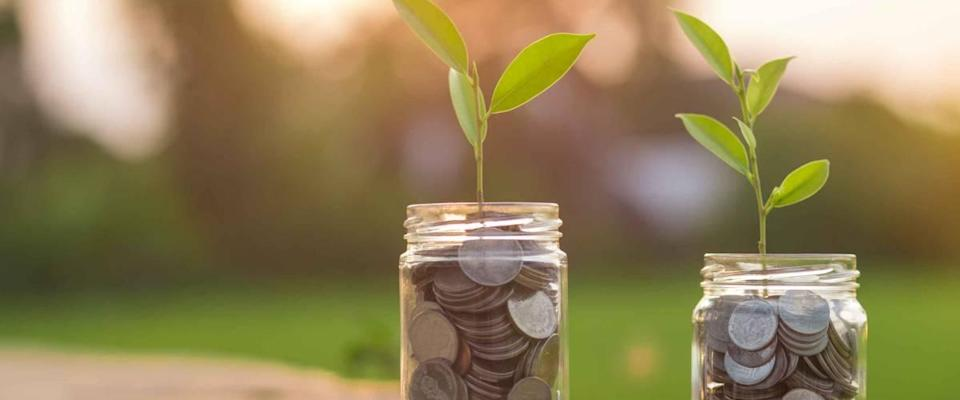 Saving money by hand puting coins in jug glass on nature background