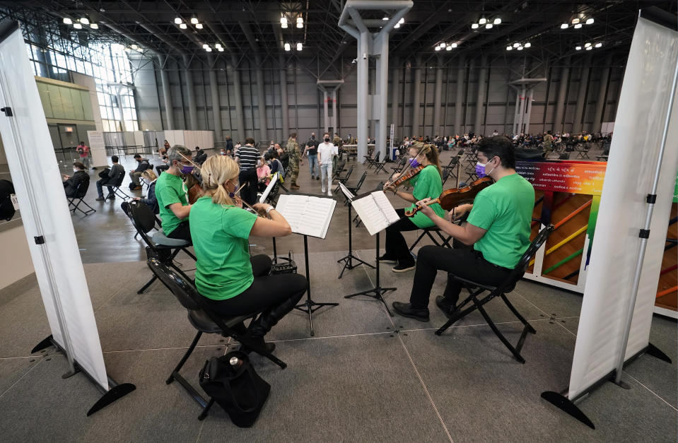 Victoria Paterson, second from right, plays with a string quartet while recently vaccinated people wait during a post-vaccination observation period inside the Jacob K. Javits Convention Center, Tuesday, March 23, 2021, in New York. (AP Photo/Kathy Willens)