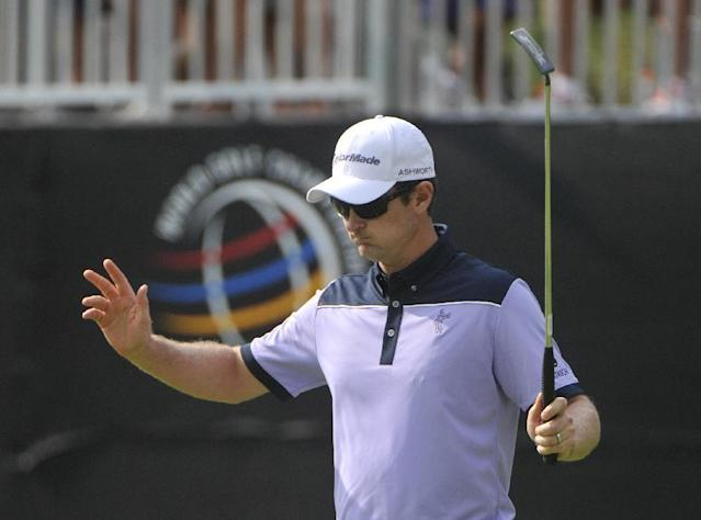 Justin Rose of England waves after making a birdie in the 16th hole, during the first round of the Bridgestone Invitational golf tournament, Thursday, July 31, 2014, in Akron, Ohio. (AP Photo/Phil Long)