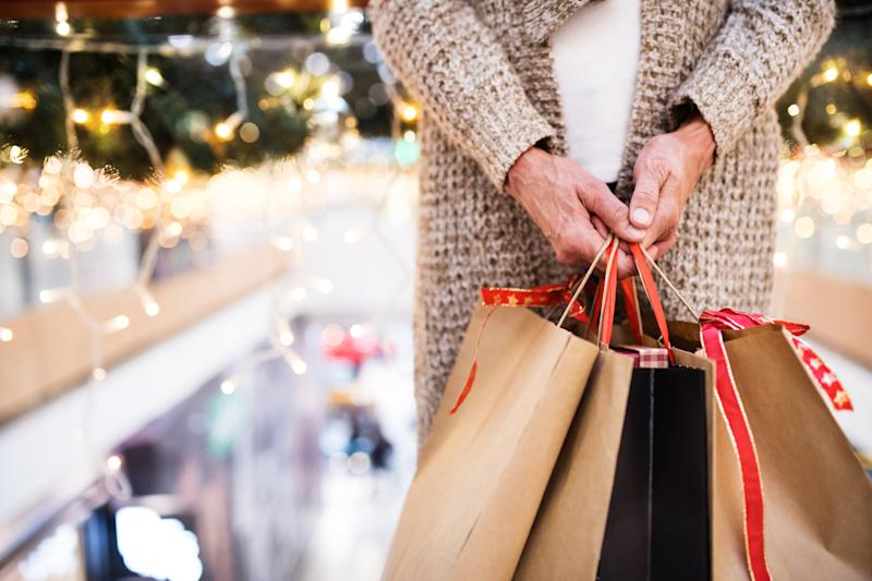Unrecognizable senior woman with paper bags doing Christmas shopping. Shopping center at Christmas time.