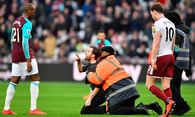 A pitch invader gestures at West Ham United's Angelo Ogbonna during last Saturday's 3-0 Premier League loss to Burnley at the London Stadium.