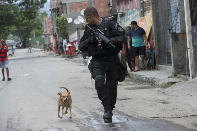"A Special Police Operations Battalion (BOPE) officer is chased by a barking dog during an operation in the Mare slum complex, ahead of its ""pacification,"" in Rio de Janeiro, Brazil, Wednesday, March 26, 2014. Elite federal police and army troops will be sent to the city to help quell a wave of violence in so-called ""pacified"" slums. Recent attacks on police bases in the favelas is raising concerns about an ambitious security program that began in 2008, in part to secure the city ahead of this year's World Cup and the 2016 Olympics. (AP Photo/Silvia Izquierdo)"