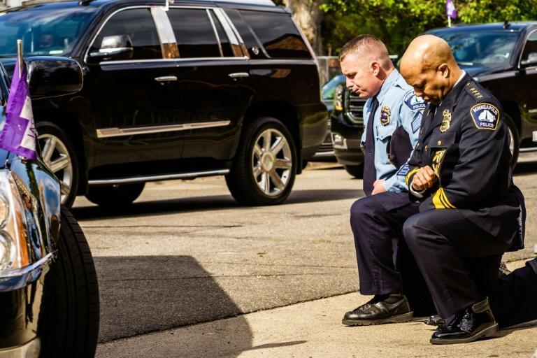 Minneapolis Police Chief Medaria Arradondo (R) kneels as the remains of George Floyd are taken to a memorial service in his honor on June 4, 2020, in Minneapolis, Minnesota.