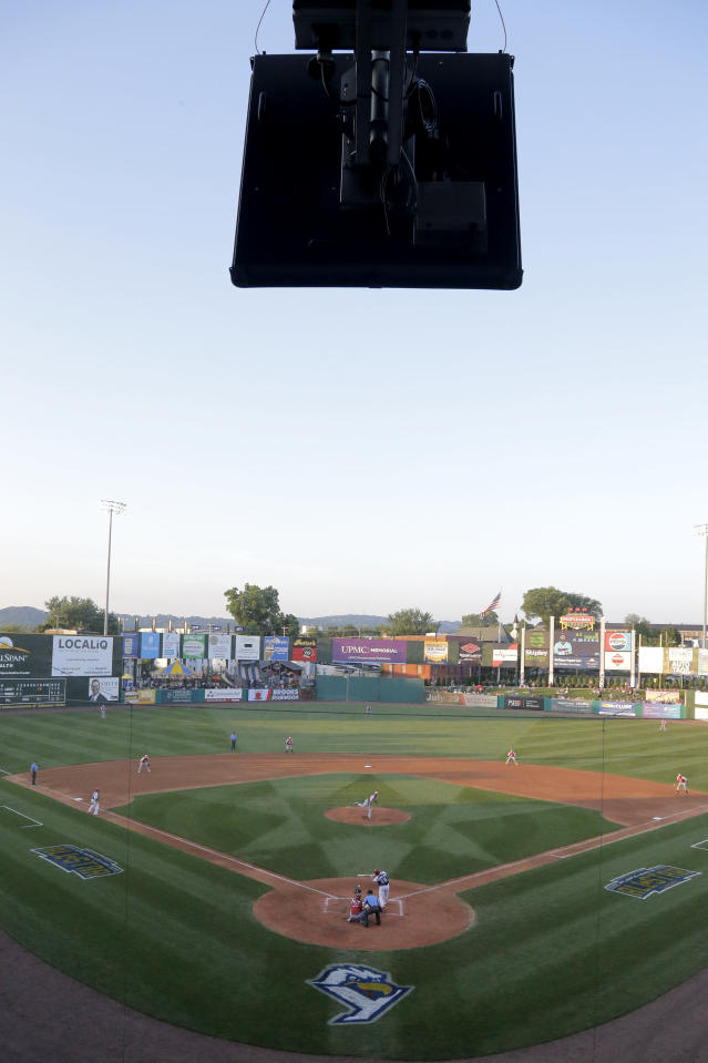 A radar device, top, is seen during second inning action in the Atlantic League All-Star minor league baseball game, Wednesday, July 10, 2019, in York, Pa. Home plate umpire Brian deBrauwere wore an earpiece connected to an iPhone in his ball bag which relayed ball and strike calls upon receiving it from a TrackMan computer system that uses Doppler radar. The independent Atlantic League became the first American professional baseball league to let the computer call balls and strikes during the all star game. (AP Photo/Julio Cortez)