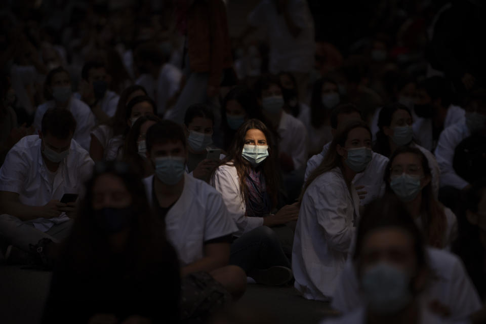 Medical residents sit in the middle of an avenue as they take part in a protest against their working conditions during a strike in Barcelona, Spain, Monday, Sept. 28, 2020. (AP Photo/Emilio Morenatti)