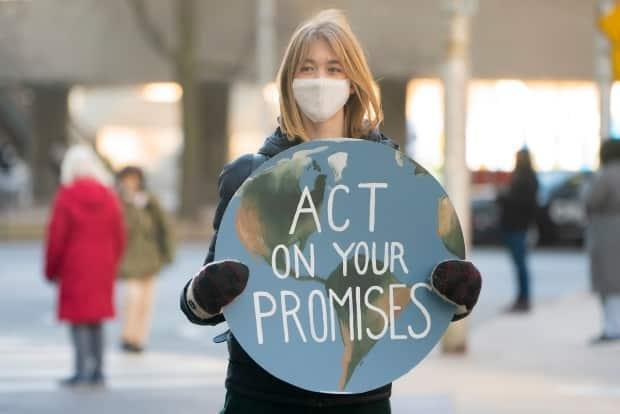 A youth climate protester carries a signat Queen Street West and Bay Street in downtown Toronto onFriday, March 19, 2021. (Sam Nar/CBC - image credit)