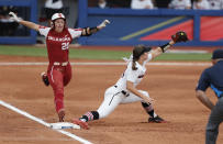 Georgia infielder Ellie Armistead (24) makes the catch at first base before Oklahoma's Jana Johns (20) runs across in the second inning of an NCAA Women's College World Series softball game on Saturday, June 5, 2021, in Oklahoma City. (AP Photo/Alonzo Adams)