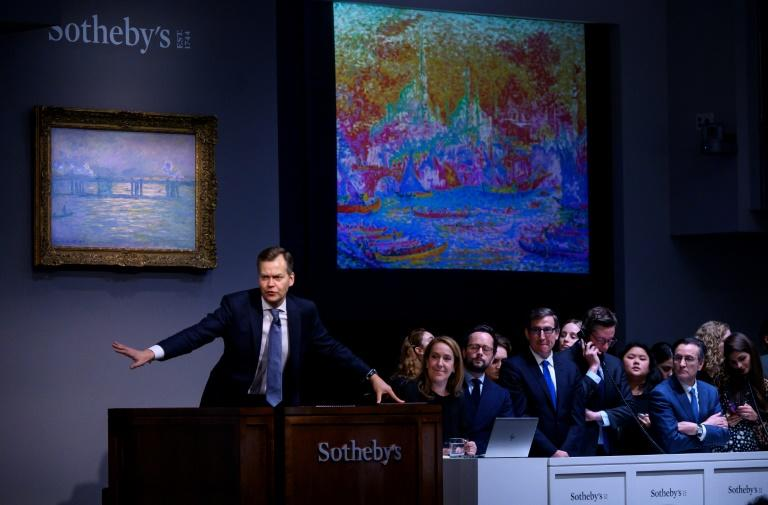 "Sotheby's auctioneer Oliver Barker takes bids on the painting by Paul Signac titled ""La Corne d'Or"" (Constantinople) during an auction on November 12, 2019 in New York"