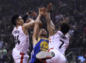 Golden State Warriors guard Klay Thompson (11) is sandwiched by Toronto Raptors guards Danny Green (14) and Kyle Lowry (7) during first half basketball action in Game 1 of the NBA Finals in Toronto on Thursday, May 30, 2019. (Frank Gunn/The Canadian Press via AP)