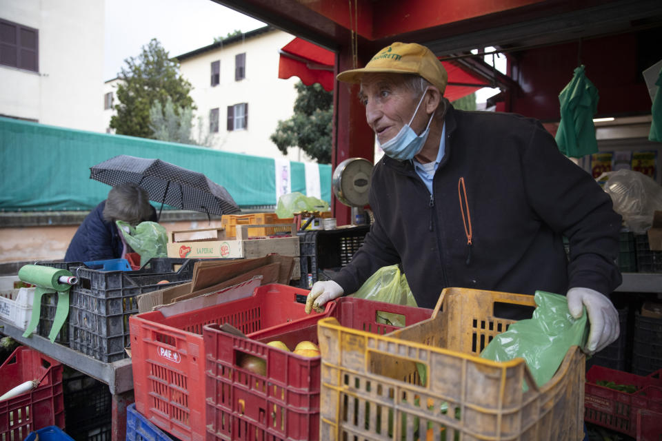 Domenico Zoccoli, 80, stands by a fruit and vegetable stand in an open air market where he works, in Rome, Wednesday, Dec. 2, 2020. In Italy, which has the world's second-oldest population, many people in their 70s and older have kept working through the COVID-19 pandemic. From neighborhood newsstand dealers to farmers bring crops to market, they are defying stereotypic labels that depict the old as a monolithic category that's fragile and in need of protection. (AP Photo/Alessandra Tarantino)