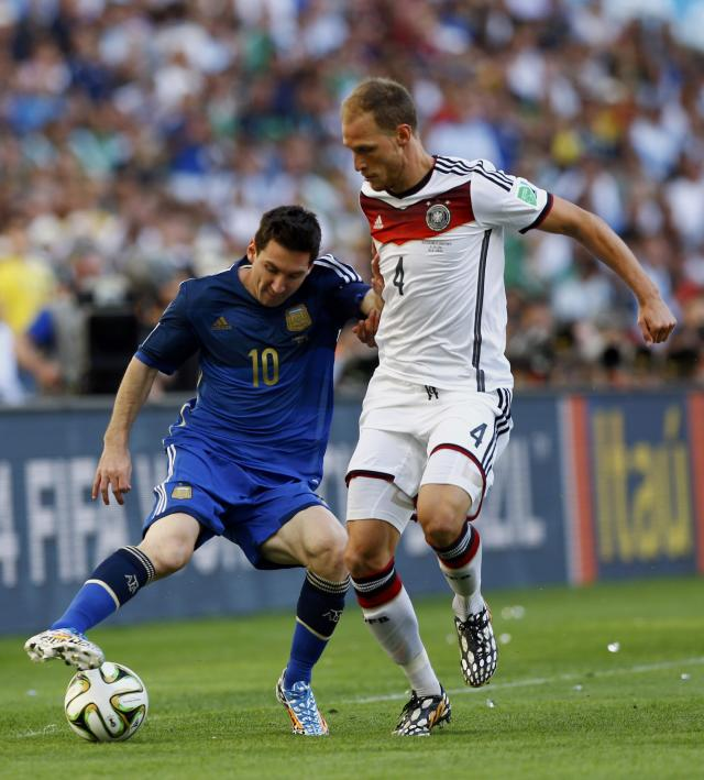 Argentina's Lionel Messi (L) fights for the ball with Germany's Benedikt Hoewedes during their 2014 World Cup final at the Maracana stadium in Rio de Janeiro July 13, 2014. REUTERS/Darren Staples (BRAZIL - Tags: SOCCER SPORT WORLD CUP)