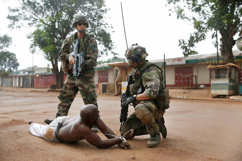 French troops detain a suspected Seleka officer , preventing Christian mobs from lynching him near the airport in Bangui, Central African Republic, Monday Dec. 9, 2013. Both Christian and Muslim mobs went on lynching sprees as French Forces deployed in the capital. The Seleka man was taken into custody by French forces who fired warning shots to disperse the crowds. (AP Photo/Jerome Delay)