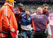 BOTTLE THROWER: A spectator is detained by security after a beer bottle was thrown on to the track during the start of the men's 100 metres final, on Day 9 of the London 2012 Olympic Games at the Olympic Stadium on August 5, 2012 in London, England. (Photo by Chris Helgren - IOPP Pool /Getty Images)