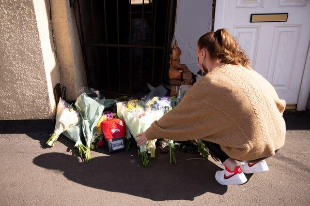 A woman leaves flowers at the scene on High Street, Brownhills