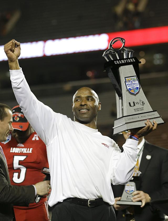 Louisville coach Charlie Strong holds the trophy after Louisville defeated Miami 36-9 in the Russell Athletic Bowl NCAA college football game in Orlando, Fla., Saturday, Dec. 28, 2013.(AP Photo/John Raoux)