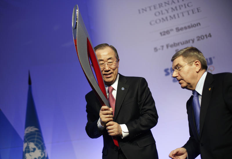 United Nations Secretary-General Ban Ki-moon, left, is handed an Olympic torch by International Olympic Committee President Thomas Bach after Ban addressed the IOC general assembly ahead of the upcoming 2014 Winter Olympics, Thursday, Feb. 6, 2014, in Sochi, Russia. It was the first time a U.N. secretary-general delivered a keynote address to the IOC's general assembly. (AP Photo/David Goldman)